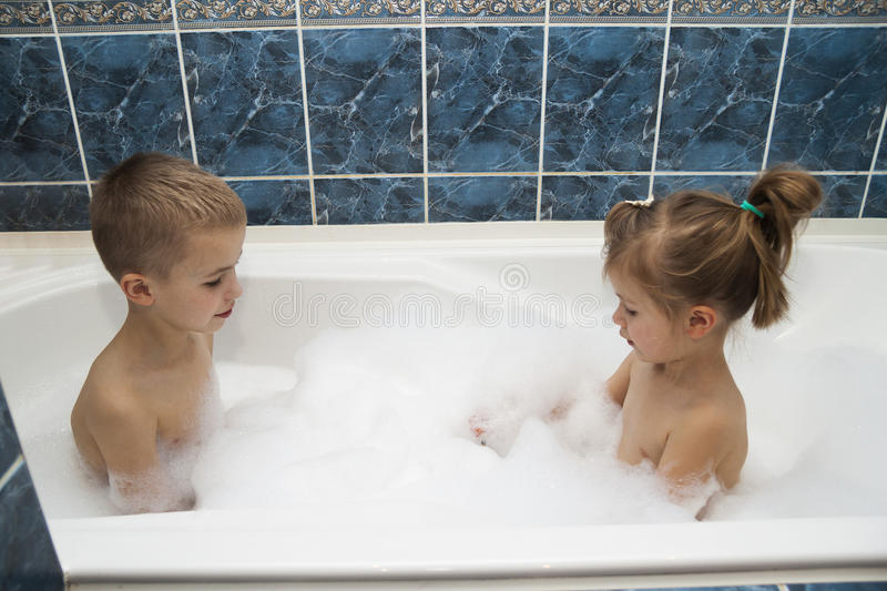Brother and sister taking a bubble bath. Little boy and girl playing. Healthcare and hygiene concept. Brother and sister taking a bubble bath. Little boy and stock photos