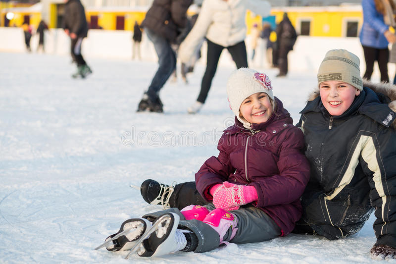 Brother and sister together fell while skating. In rink royalty free stock photography