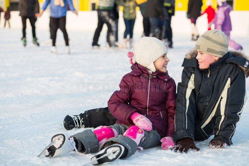 Brother and sister together fell while skating. At winter stock photos