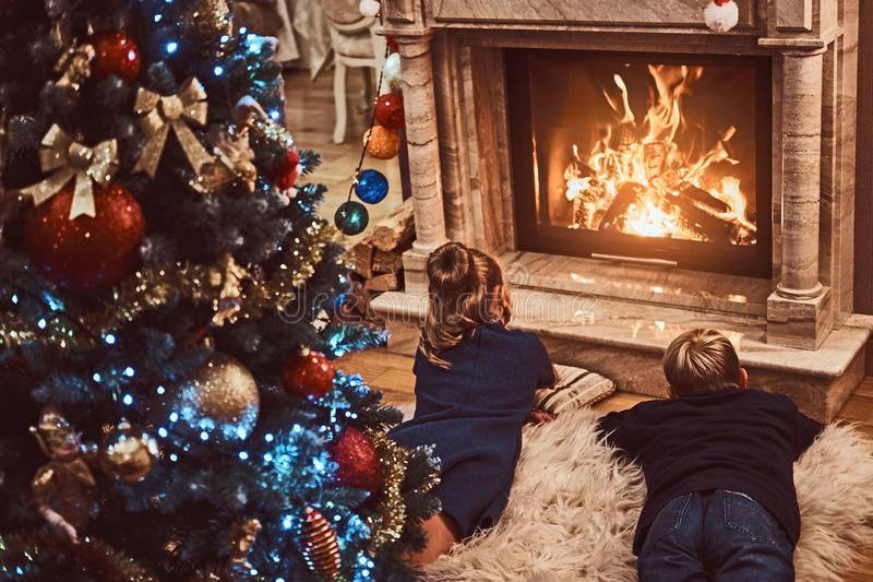 Back view, brother and sister warming next to a fireplace in a living room decorated for Christmas. stock photography