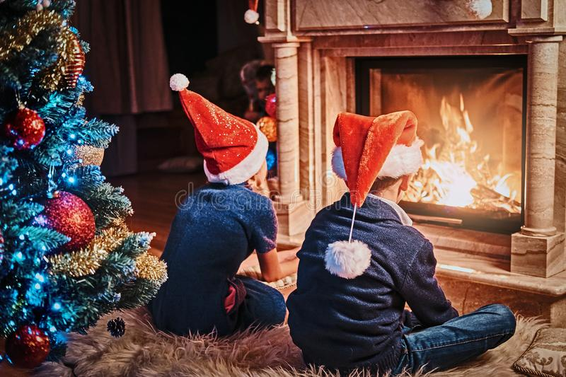 Back view, brother and sister wearing Santa`s hats warming next to a fireplace in a living room decorated for Christmas. Brother and sister wearing Santa`s hats stock photography