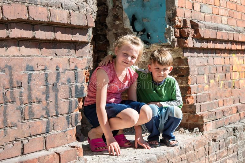 Brother and sister were left alone as a result of military conflicts and natural disasters. Children in a ruined and abandoned. House. Staged photo royalty free stock image