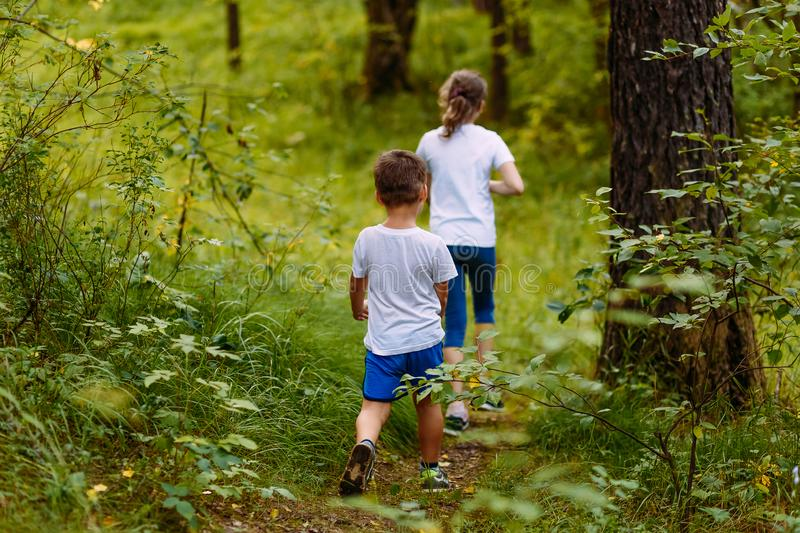 Brother and sister in white t-shirts go into the woods on the path in the summer. Outdoors royalty free stock photos