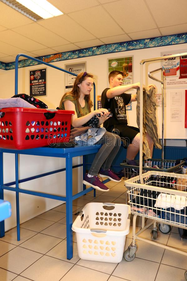 Teenagers folding clothes in a laundromat royalty free stock image