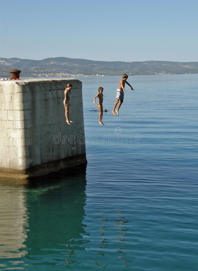 Download Brother And Sisters Jumping In Water Stock Photo - Image: 12454088