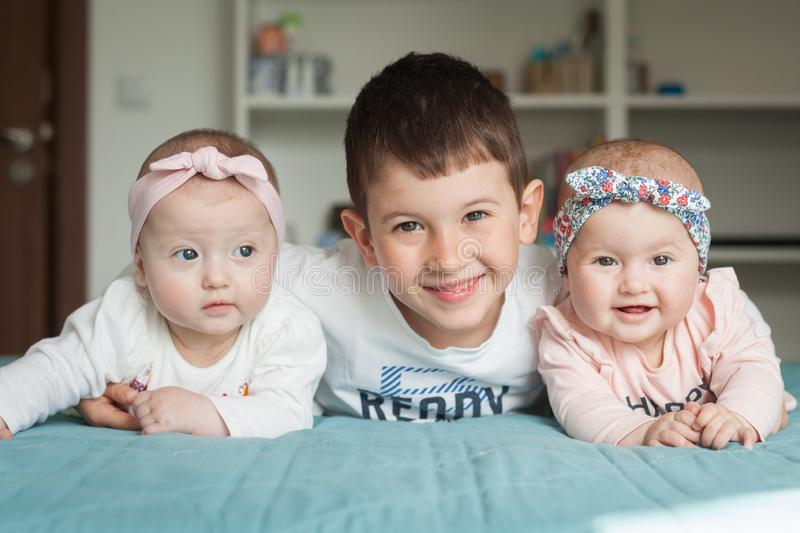 Brother and sisters lie on the bed and smiling. Brother embraced his little twin sisters. They are very happy with each other stock image