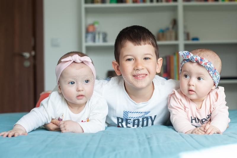 Brother and sisters lie on the bed and smiling. Brother embraced his little twin sisters. They are very happy with each other. Brother and sisters lie on the bed royalty free stock images
