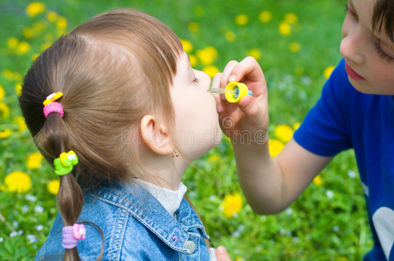 Brother spraying nose his sister royalty free stock images