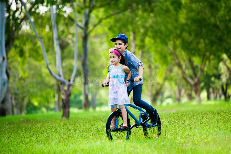Brother taking his sister on a bike ride stock image