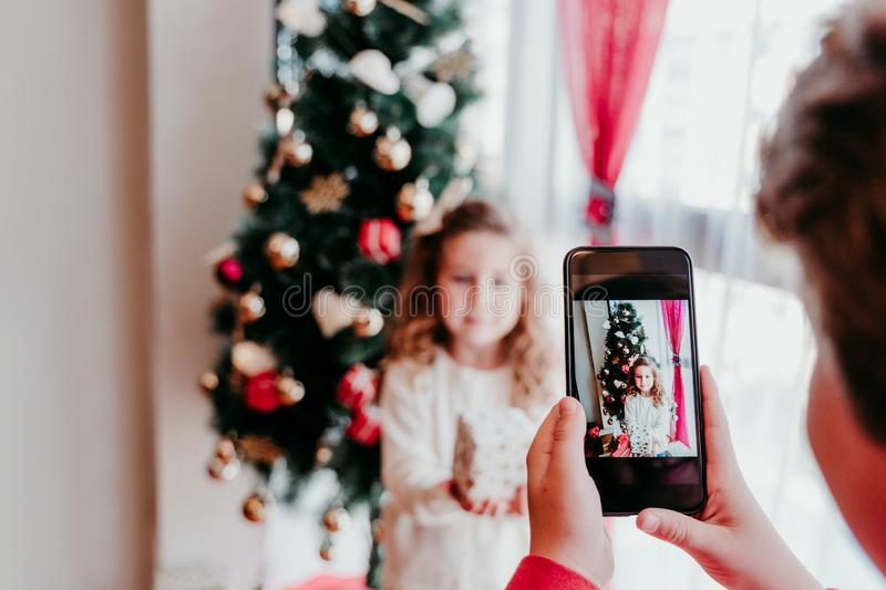 Brother taking a picture of his sister with mobile phone at home. Girl standing by the christmas tree. Family time. Christmas. Concept, technology, portrait royalty free stock images