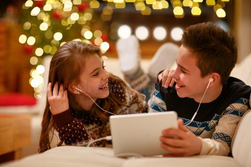 Brother y hermana con los auriculares que mienten y que usan una tableta y foto de archivo libre de regalías