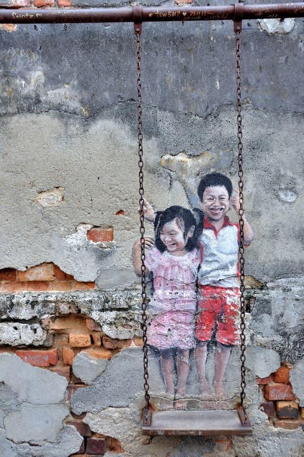 €œBrother y hermana del arte de la calle de Penang en un  de Swing†foto de archivo