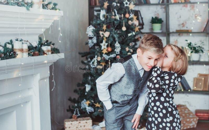 Brother y hermana en la sala de estar en el fondo del árbol de navidad Los niños festivamente se vistieron imagenes de archivo
