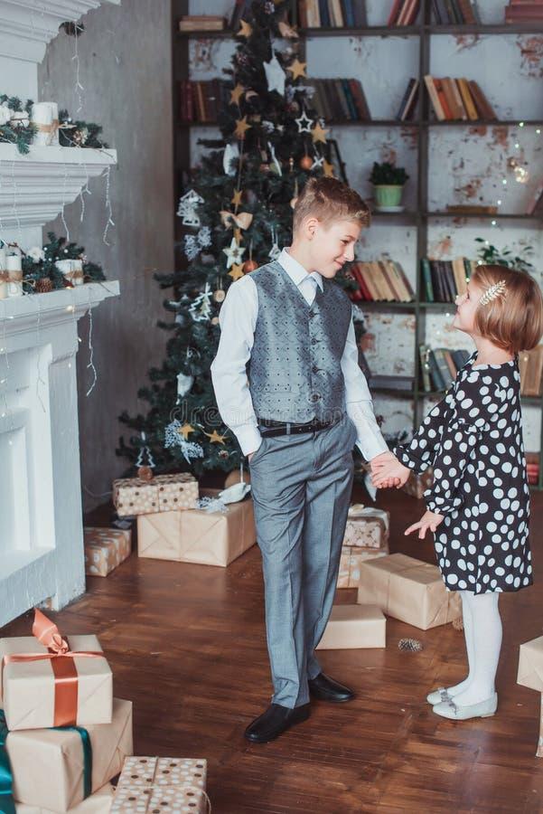Brother y hermana en la sala de estar en el fondo del árbol de navidad Los niños festivamente se vistieron imagen de archivo libre de regalías