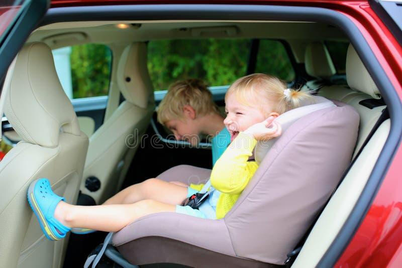 Brother y hermana que disfrutan de viaje en el coche imagenes de archivo
