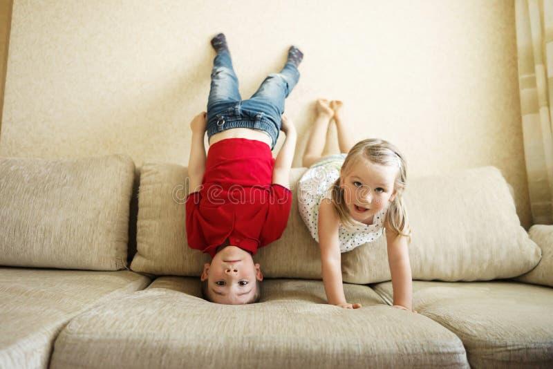 Brother y hermana que juegan en el sofá: el muchacho se coloca al revés fotografía de archivo