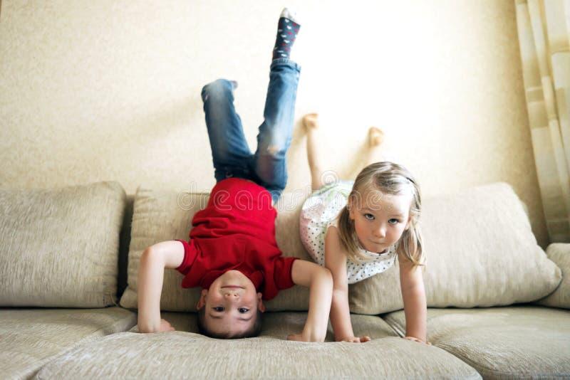 Brother y hermana que juegan en el sof?: el muchacho se coloca al rev fotos de archivo