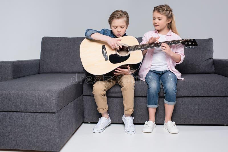 Brother y hermana que juegan en la guitarra junto mientras que se sienta en el sofá fotos de archivo