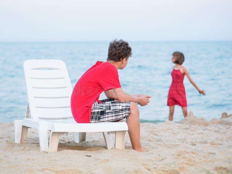 Brother y hermana que juegan en la playa foto de archivo