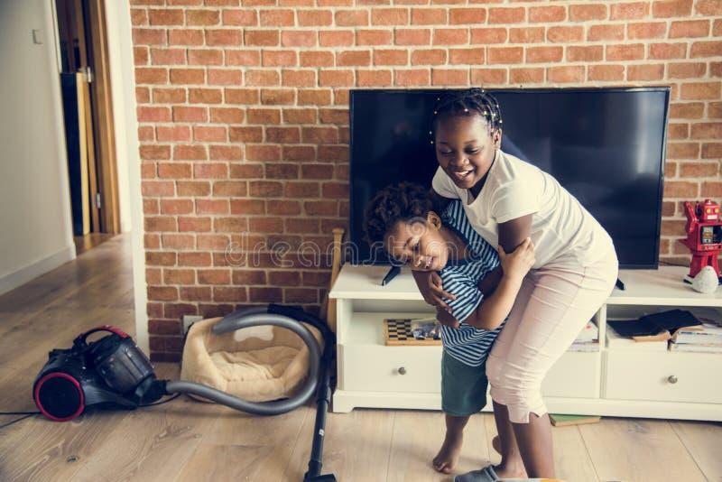 Brother y hermana que juegan junto en casa imagenes de archivo
