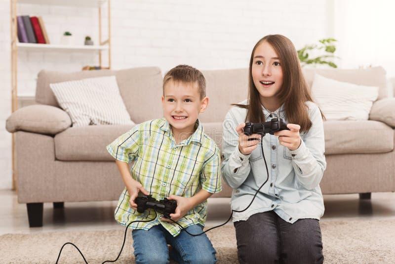 Brother y hermana que juegan a los videojuegos juntos fotografía de archivo