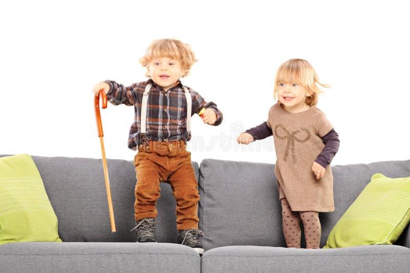 Brother y hermana que se colocan y que juegan en un sofá fotos de archivo