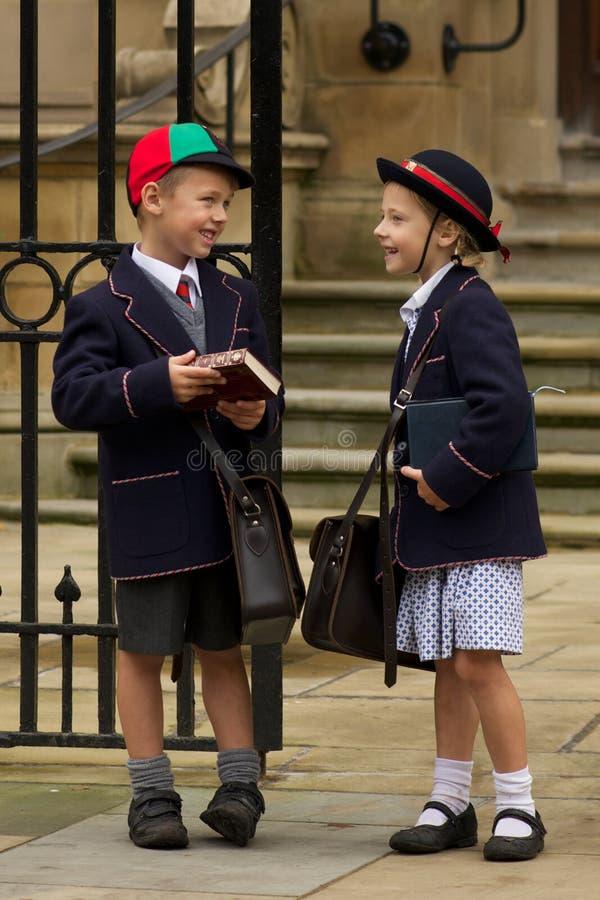 Brother y hermana que se ríen de las puertas de la escuela foto de archivo