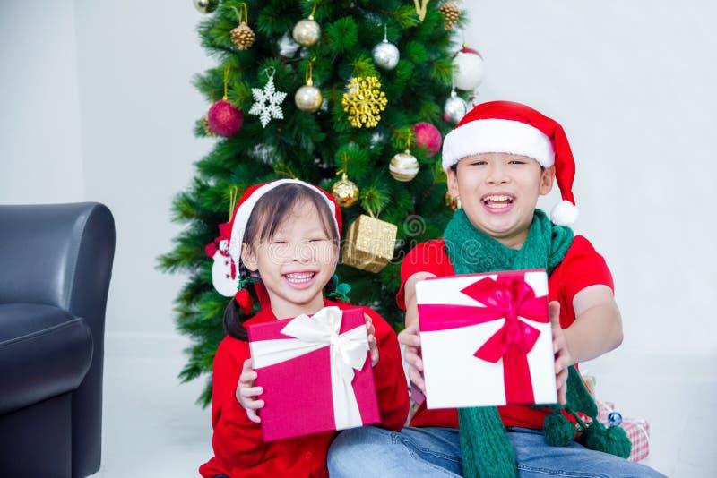 Brother y hermana que sostienen las actuales cajas y que sonríen así como la decoración de la Navidad foto de archivo