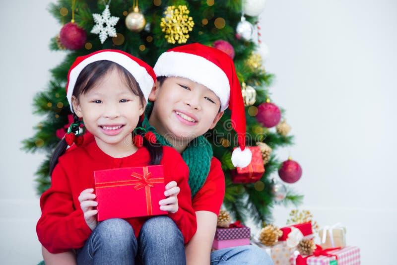 Brother y hermana que sostienen las actuales cajas y que sonríen así como la decoración de la Navidad imagen de archivo libre de regalías
