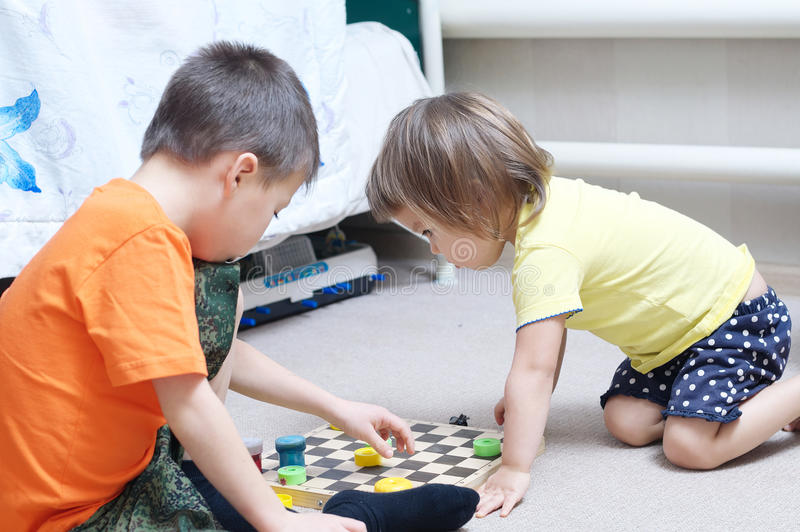 Brother y la hermana que juegan juntos, los hermanos juegan a casa en ajedrez fotografía de archivo libre de regalías