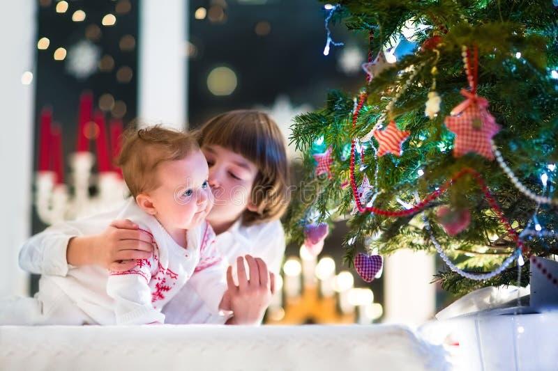 Brother y su hermana del bebé que juegan junto en un árbol de navidad foto de archivo