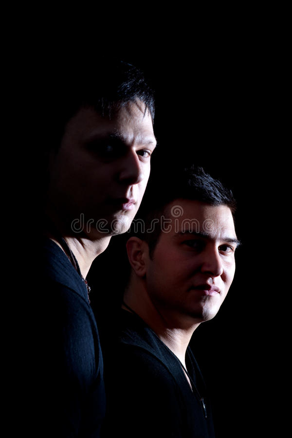 Brothers. Two brothers isolated on black. Dramatic lighting stock images