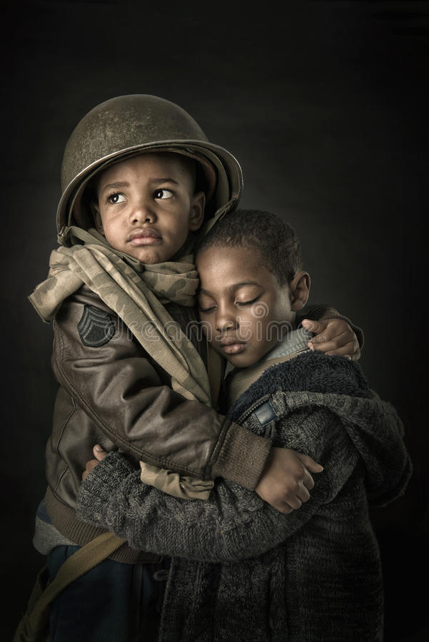 Brothers in arms. Dramatic portrait of boy soldier protecting his young brother