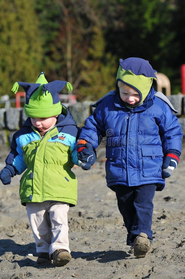 Brothers on the beach. Young boys, brothers, holding hands on the beach as they walk on a cold day in Vancouver. Fleese hats and warm jackets stock image