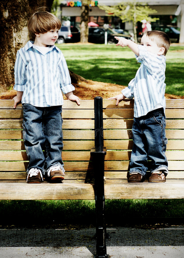Brothers on Benches. Two young identically dressed brothers standing on a park bench. Vertically framed, high-contrast shot royalty free stock images