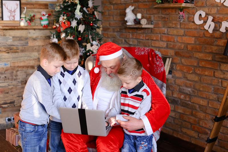 Close friends of children with Santa Claus use laptop in Christ. Brothers boys and sister girl help old Christmas grandfather to choose interesting gifts for royalty free stock images
