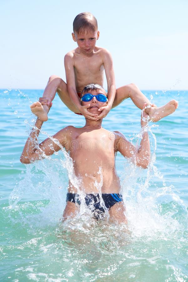 BROTHERS BOYS 14 and 7 years old PLAY IN SEA WATER, SUMMER stock photography