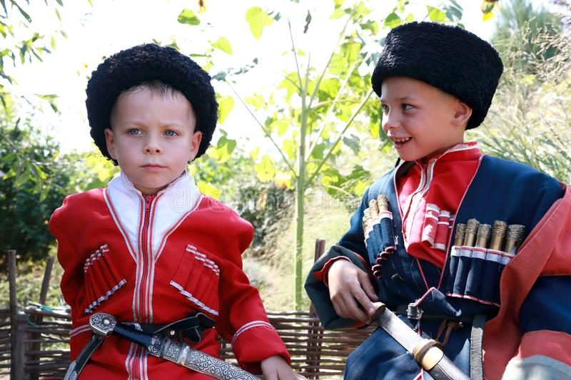 Brothers in Cossack costumes. Portrait of brothers in Cossack costumes in backyard stock image