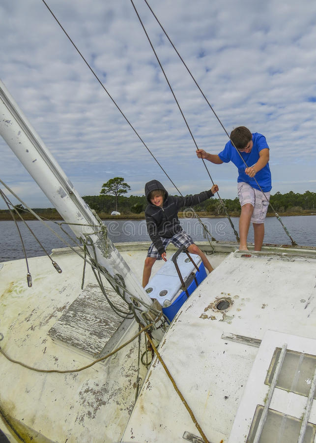 Brothers Explore Wrecked Sailboat stock photos