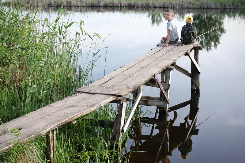 Brothers fishing on the river bank. Kids siting with sticks in hands. stock photo