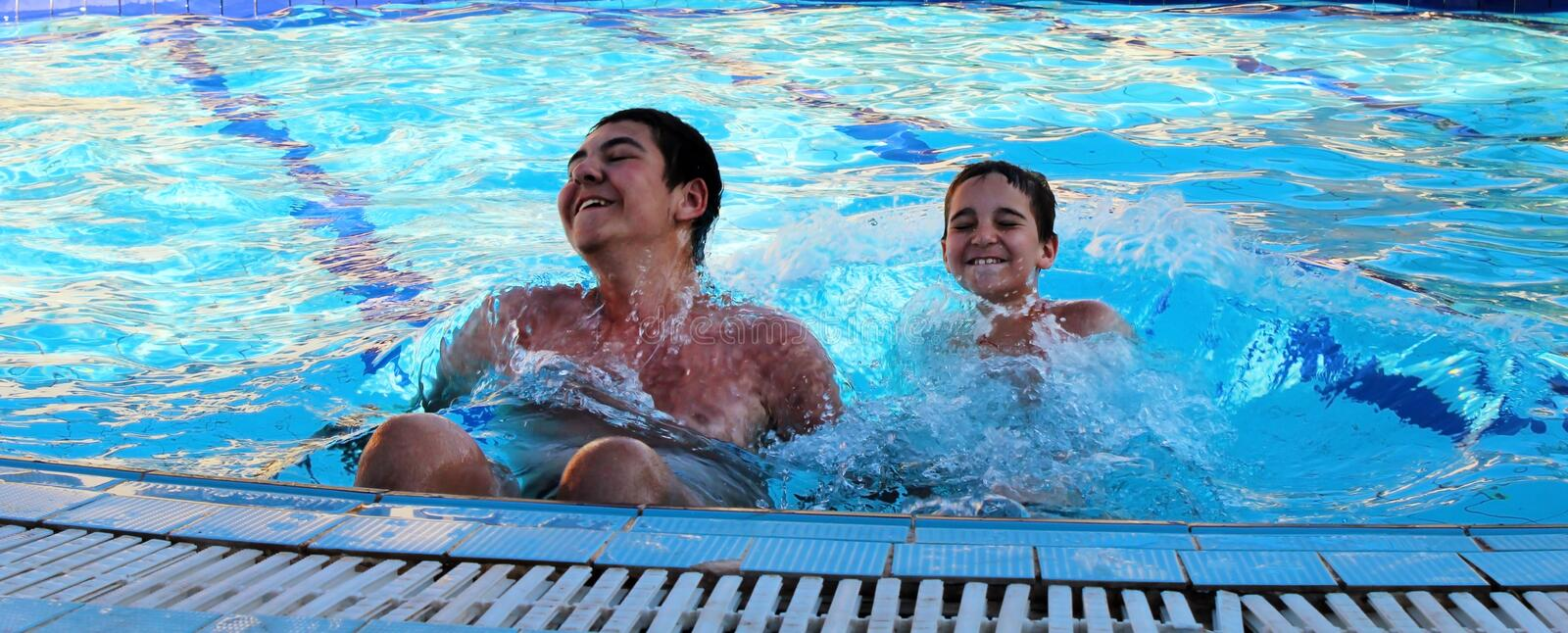 Brothers  have fun in the pool. Brothers play and have fun in the pool royalty free stock photo