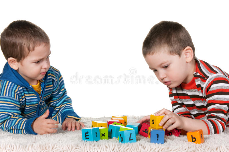 Brothers playing blocks on the carpet stock photos