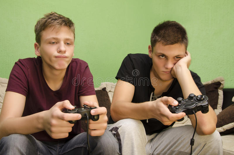 Brothers playing video games boredom. Two Caucasian brothers bored from playing video games royalty free stock image
