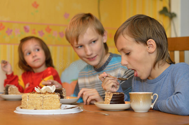 Brothers and sister eating cake. At home stock photos