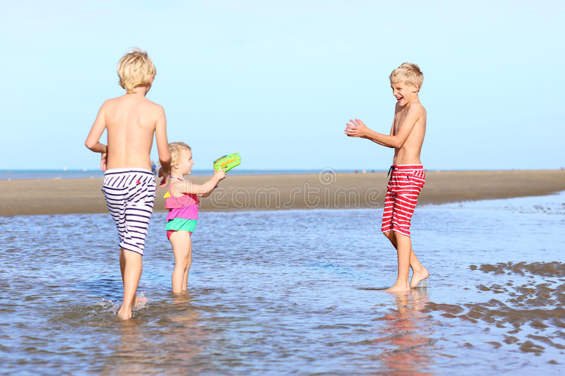 Brothers and sister playing on the beach royalty free stock image