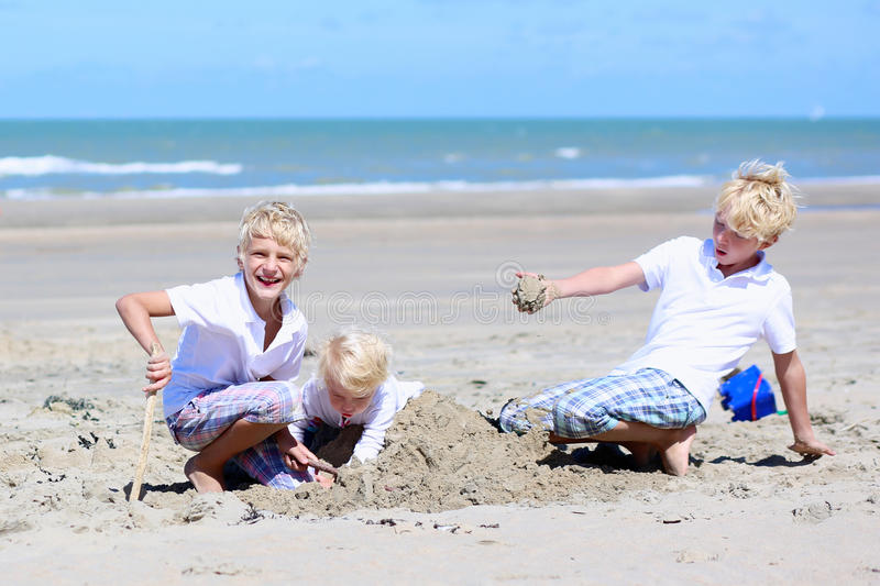 Brothers and sister playing on the beach stock photos