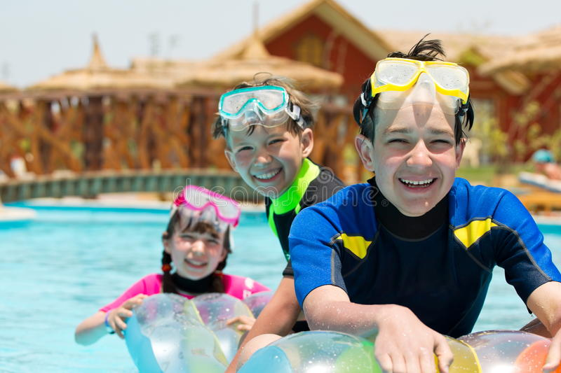 Brothers and sister in pool. Two brothers and their sister on holiday in a swimming pool. All have swim goggles on royalty free stock images
