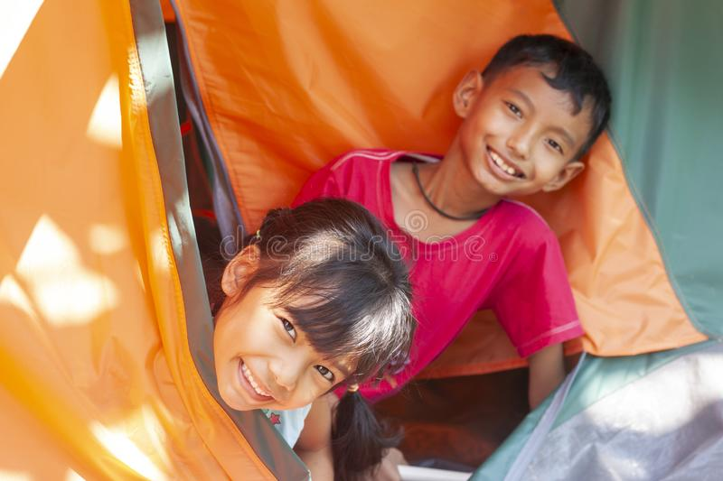 The brothers and sisters in tents while traveling go camping in holiday. royalty free stock photography