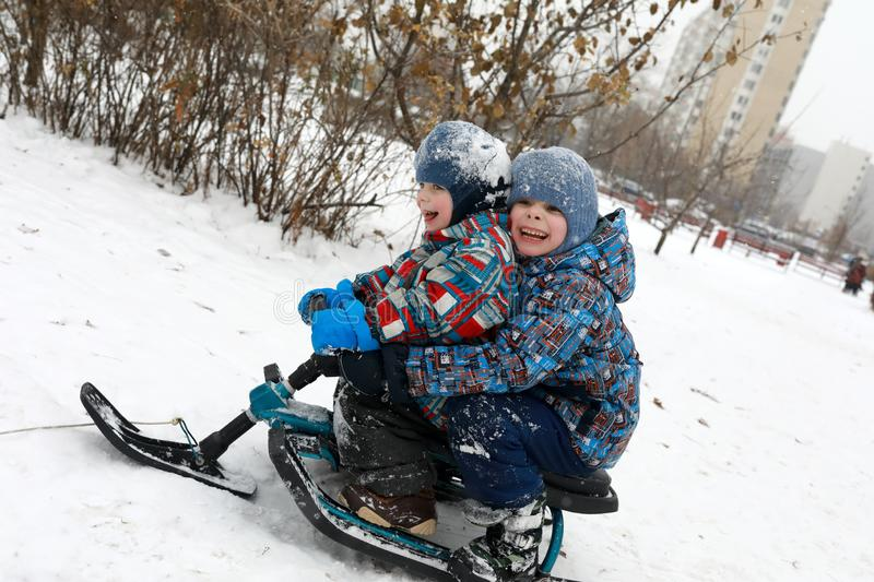 Brothers sitting on snow scooter royalty free stock photo