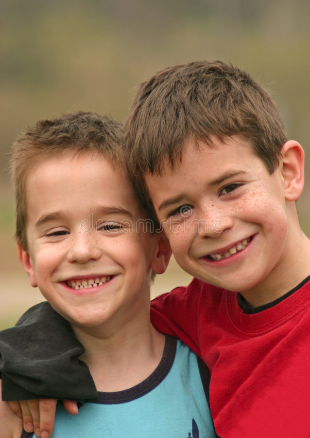 Brothers Smiling. Two Brothers smiling with their arms around each other royalty free stock image
